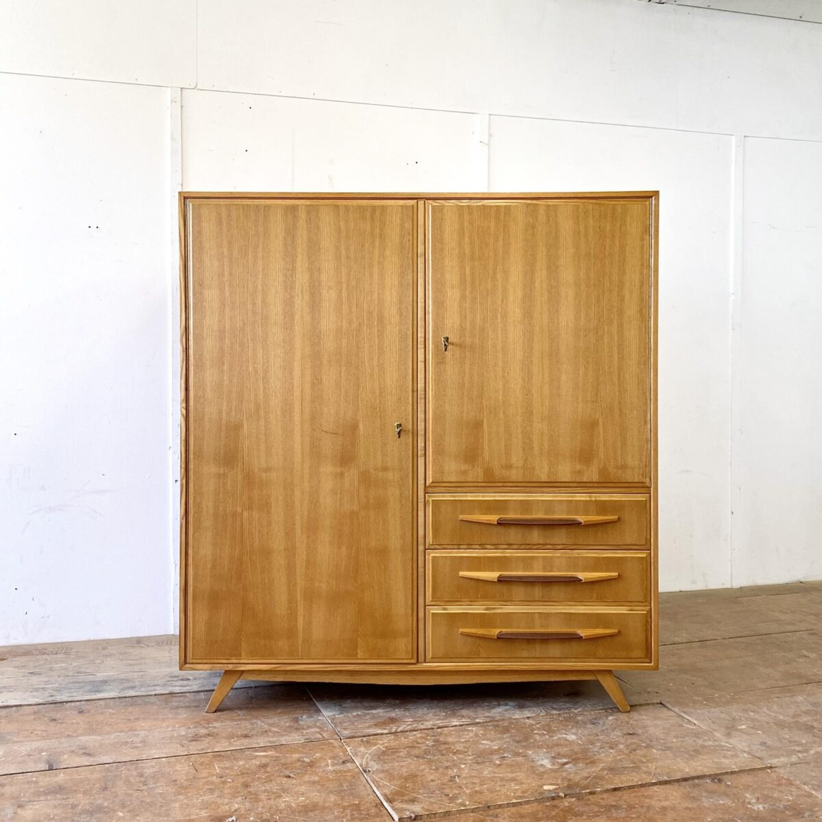 Deuxieme.shop swissdesign Schrank 50s. Schweizer Kleiderschrank Eschenholz furniert, von Corta Multiform aus den 50er Jahren. 140x57cm Höhe 153cm. Der Schrank ist in schönem Original Zustand, die violett-braunen Schubladengriffe sind aus Kunstleder. Hinter den Türen befinden sich Tablare und eine Kleiderstange.