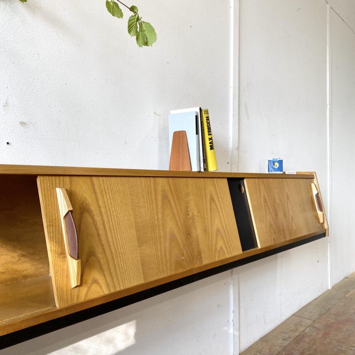 Deuxieme.shop swissdesign Lowboard Wall Board. Längliches Wandregal mit Schiebetüren, Eschenholz furniert, mit Kunstleder griffen. Von Corta Multiform aus den 50er Jahren. 193x27cm Höhe 32.5cm die tiefe der Deckplatte ist 19cm. Das Regal ist in gutem allgemein Zustand, die Unterseite ist nicht furniert. Durch die abgeschrägte Front eignet es sich als Lowboard.