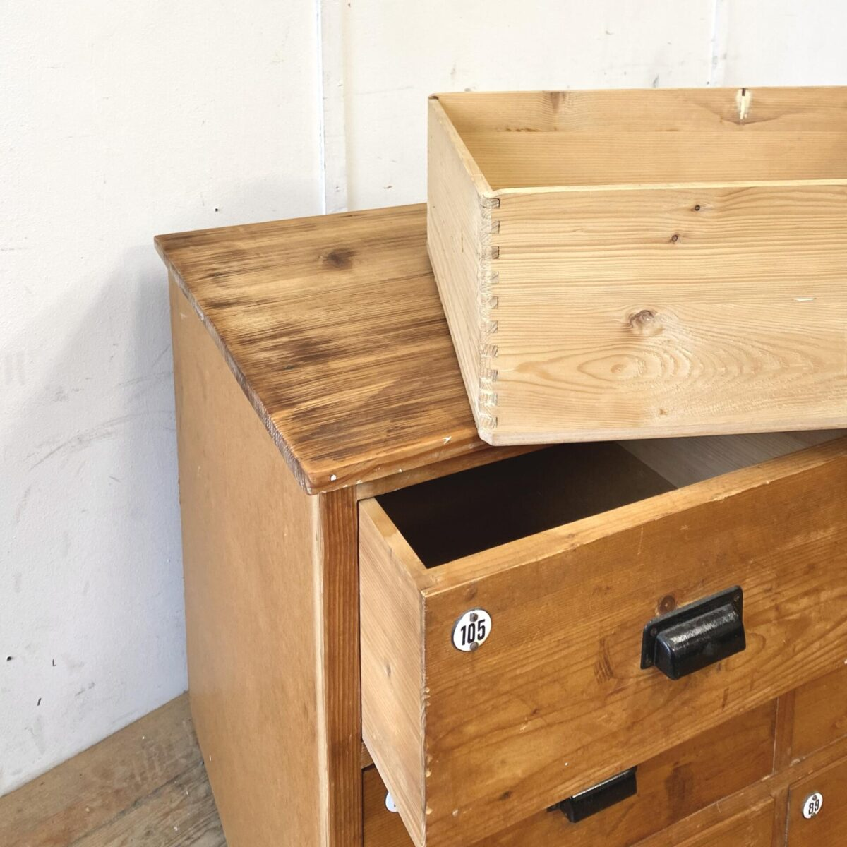 Deuxieme.shop industrial Schubladenkorpus. Schubladenmöbel aus Tannenholz mit schwarzen Muschelgriffen und Emaille Nummern. 203x67cm Höhe 79cm. Die Seiten und Rückwand der Kommode ist aus Pavatex, Schubladenböden ebenfalls. Geeignet für Kleider oder Wohnzimmer, als Werkstatt Möbel sind die Schubladen wohl zu wenig robust.