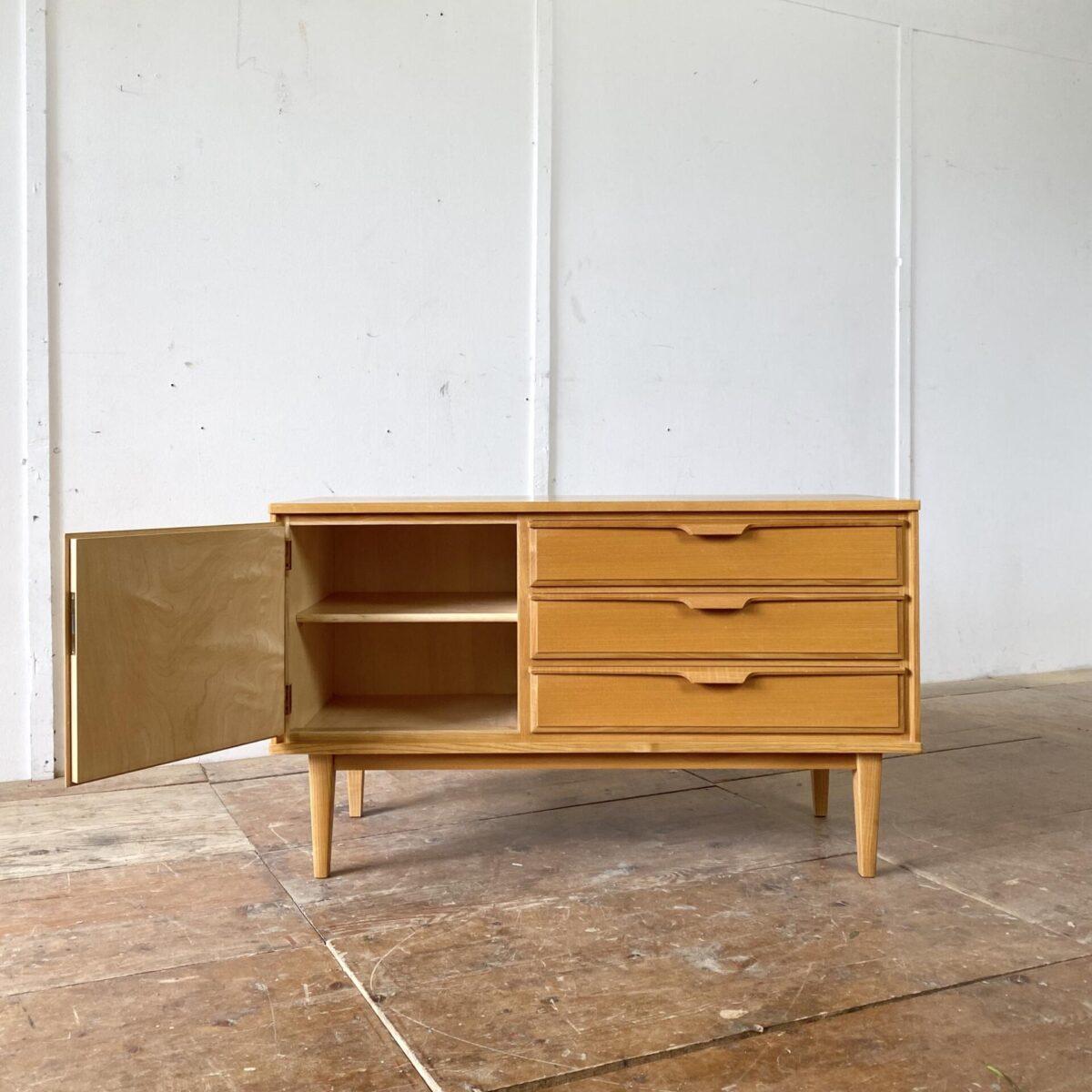 Deuxieme.shop swissdesign Sideboard 60er Jahre. Eschenholz Sideboard mit drei Schubladen und abschliessbarer Türe. 110x43cm Höhe 64cm. Die Schubladen sind aus Vollholz mit länglichen Holz Schubladengriffen. Die Kommode steht, mit schöner Bodenfreiheit, auf konischen Beinen.
