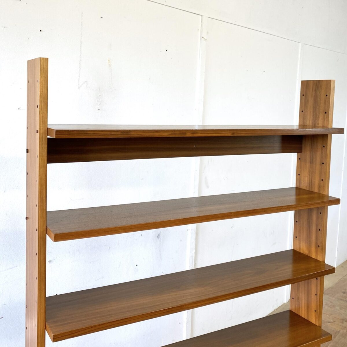 Deuxieme.shop swissdesign bookshelf 60er Jahre. Schweizer System Bücherregal Nussbaum furniert. 99x30cm Höhe 170cm. Die Tablare sind höhenverstellbar, der Stauraum unten ist per Klappe zugänglich.