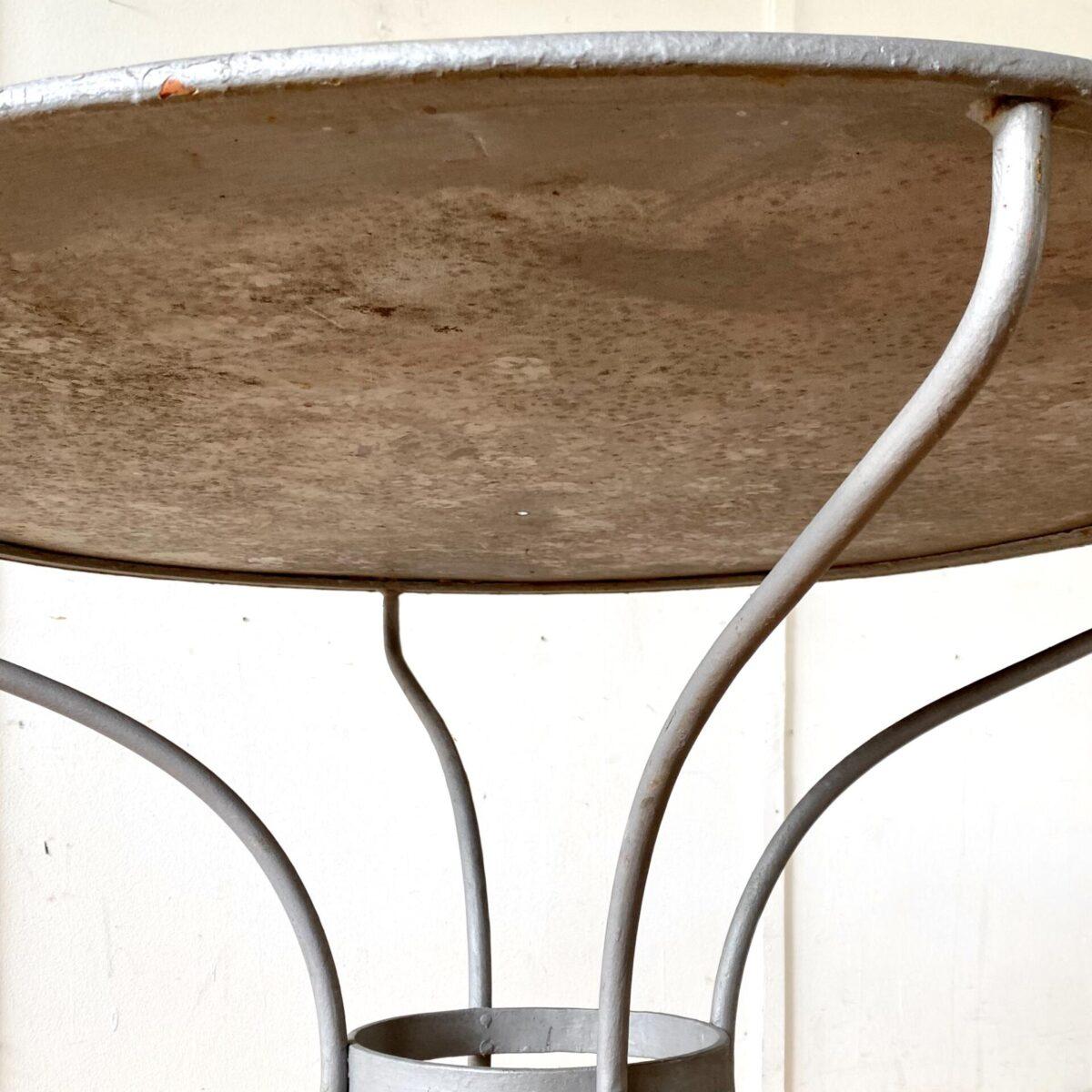 Deuxieme.shop antiker Metall Gartentisch designklassiker. Runder Jugenstil Metall Gartentisch. Durchmesser 91cm Höhe 75cm. Das Tischblatt ist etwas uneben und hat ein kleines Loch. Der Tisch wurde mal angemalt, ich tippe auf eine Zinkgrundierung, keine gröberen Roststellen oder Durchrostungen. Wäre auch eine gute Basis um das Tischblatt in einer Wunschfarbe zu malen oder lackieren.