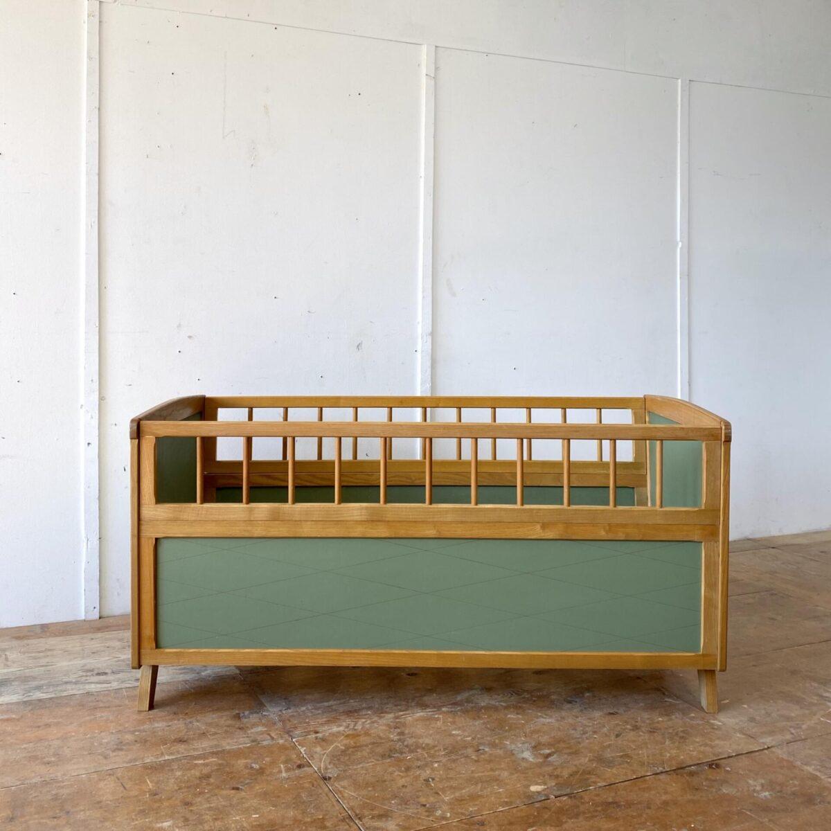Deuxieme.shop vintage Kinderbett 60er Jahre swissdesign. Kinderbett aus Esche mit grünen Pavatex Füllungen. 150x82cm Höhe 78cm. Eine passgenaue Matratze müsste 145x68.5cm haben. Das Bett kann einfach zusammen gesteckt werden, die oberen zwei Sprossenelemente können weggenommen werden. Das Bett ist in sauberen stabilen Zustand.