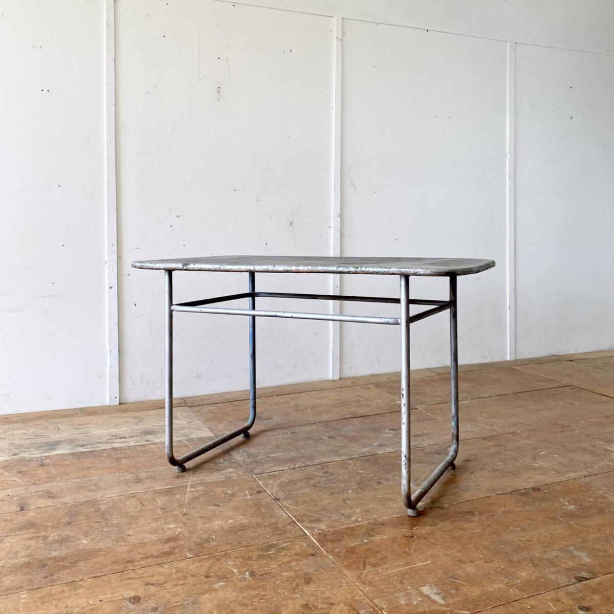 Deuxieme.shop Embru Bigla Gartentisch Swiss designklassiker. Vintage Metall Gartentisch mit gebogenem Stahlrohr Gestell. 120x70cm Höhe 76cm. Das Tischblatt ist ziemlich eingebeult, könnte mit einem Blech neu belegt werden. Die Patina und Unebenheit hat aber auch ihren Reiz. Die Stahlkufen haben angeschnittene Kugel Füsse. Ein Hersteller ist nicht ersichtlich, Ähnliches haben wir von Bigla oder Embru gefunden.