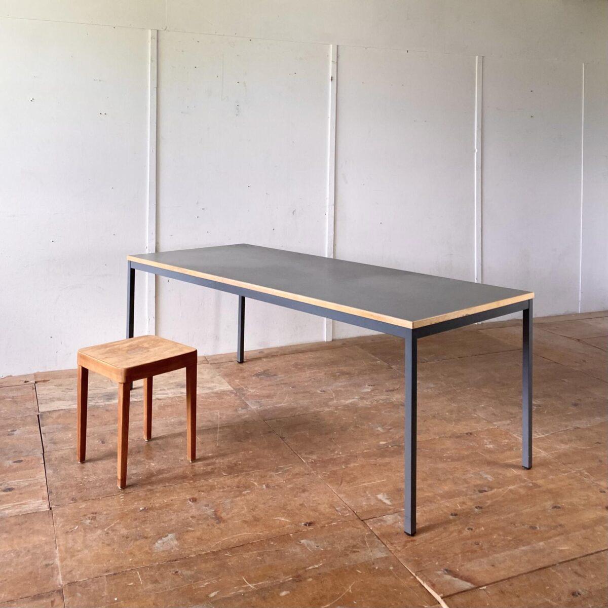 Deuxieme.shop Vintage Linoleum Tisch. Einfacher Arbeitstisch mit grau lackierten Metallbeinen. 200x80cm Höhe 73.5cm. Das Tischblatt mit grauem Linoleum und Holz Kante, hat diverse kleinere hicke und Abnutzungserscheinungen.