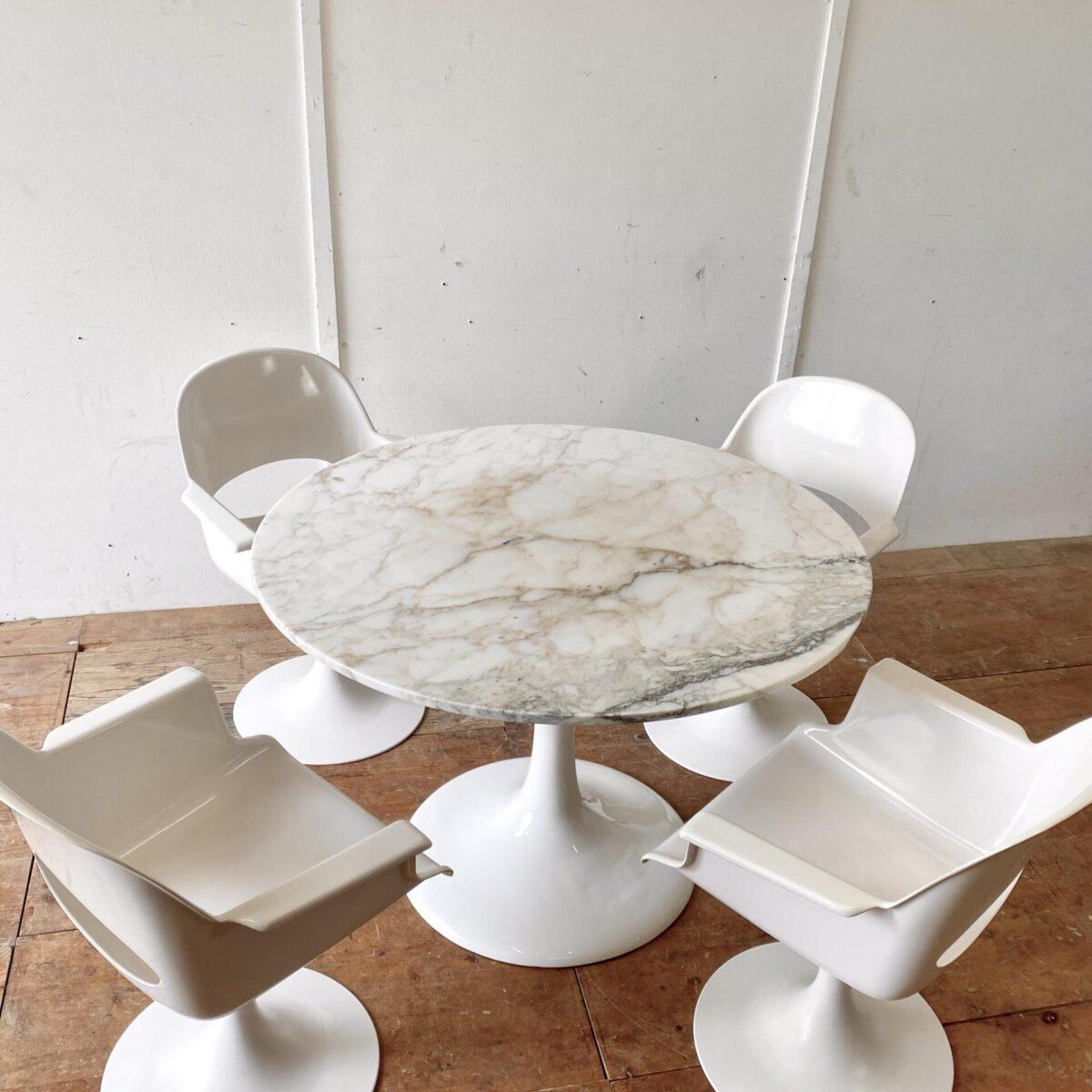 Deuxieme.shop midcentury eero saarinen Marmor Tisch. Space age Schalensitz Stühle mit Tulpenfuss aus den 70er Jahren. Preis fürs 4er Set. Die Stühle sind drehbar, und wurden in Deutschland von der Firma Kurz hergestellt. Eine Rückenlehne hat einen kleinen Riss scheint aber stabil zu sein, ansonsten in gutem allgemein Zustand. Der runde Marmor Tisch mit Tulip Fuss ist ebenfalls verfügbar. Preis: 1100.- Durchmesser 110cm Höhe 73.5cm. Ein Hersteller ist uns nicht bekannt. Der Tulpenfuss ist Emailliert und recht schwer, sieht nach Aluminiumguss aus. Die weisse Emaille Oberfläche ist in schönem Zustand.