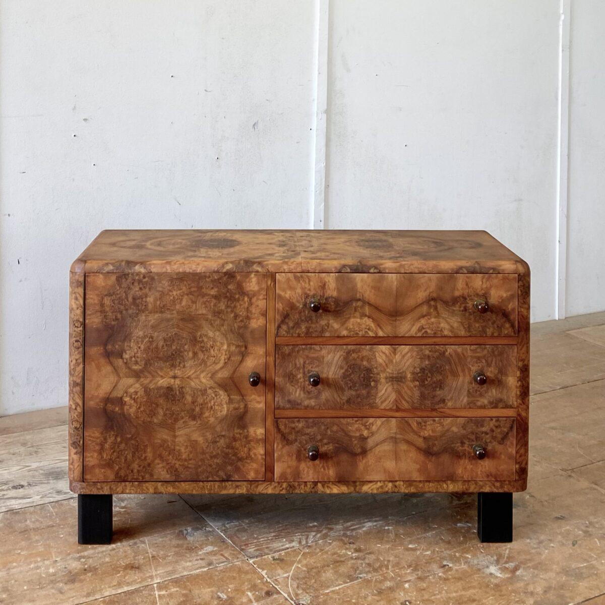 Nussbaum Kommode im Art déco Stil. 110x45cm Höhe 67cm. Das Möbel ist mit Wurzelholz furniert, die runden Kanten sind aus Vollholz, Griffe aus gegossenem Kunststoff oder Bakelit. Die Holz Oberflächen sind mit Naturöl behandelt. Hinter der Türe befindet sich ein Tablar, die oberste Schublade ist in 4 Fächer eingeteilt.