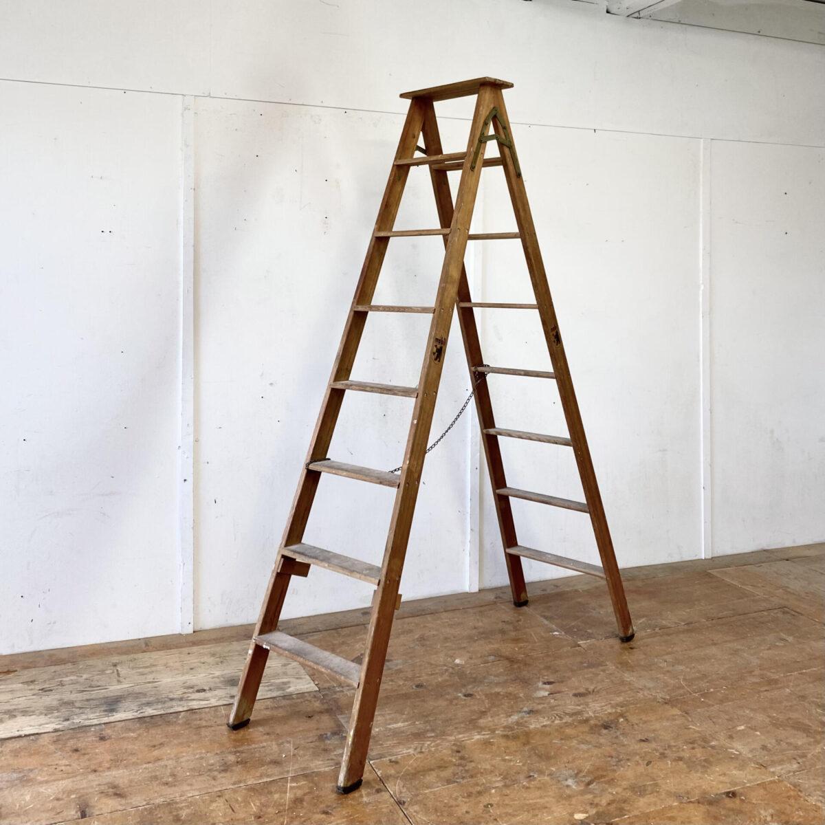 Alte Bockleiter aus Holz mit 8 Sprossen. Oberste Tritthöhe 200cm. Die Leiter ist in stabilem und noch Einsatz fähigem Zustand. Die Metallkette hat keine technische Funktion und kann auch abgenommen werden.