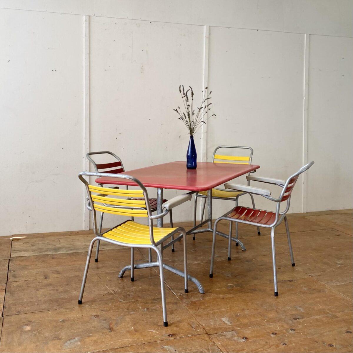 Deuxieme.shop 60er jahre. Klappbarer Metall Gartentisch von Bigla. 140x80cm Höhe 70cm. Der Tisch hat etwas Rost auf der Unterseite, Oberfläche sonnenverbleicht und Patina. Ansonsten in gesundem Zustand keine Durchrostungen. Vier Gartenstühle mit Kunststoff Lättli und Armlehnen, von Schaffner oder Bättig. Die Armlehnen sind etwas fleckig, ansonsten in gutem gereinigtem vintage Zustand. Die Stuhlbein Kappen sind durch neue ersetzt. Der Preis gilt fürs Set.