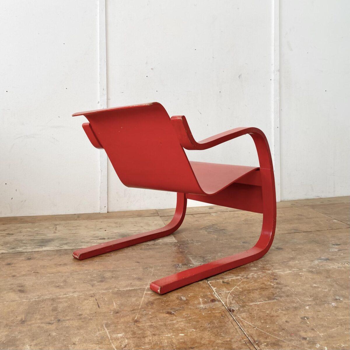 Deuxieme.shop Alvar Aalto Freischwinger Sessel. Modell 31 Birke Formsperrholz. Der Sessel ist etwas asymmetrisch (verzogen) was bei älteren Modellen öfters so ist. Im Bild 4 gut zu sehen. Die rote Farbe ist etwas abgewetzt, und mehrere Farbabplatzer an diversen Stellen.