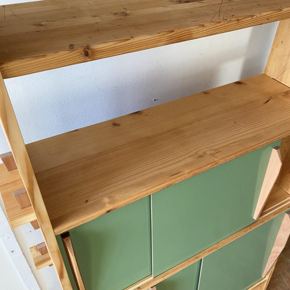 Nicola Landert für deuxieme.shop Steckbares Bücherregal mit Schiebetüren. 100x40cm Höhe 197cm, die obere Tablar Tiefe ist 21cm. Das Regal wurde von uns gezeichnet und produziert, wir haben gebrauchtes Material aus unserem Fundus verwendet. Regalböden und Seitenwände sind aus Fichtenholz. Keile und Schiebetürgriffe sind aus Buchenholz. Die alten grauen Kelko Schiebetüren sind auf der einen Seite Grün lackiert, und lassen sich wenden, die Griffe müssen dabei auf die andere Seite montiert werden. Im unteren Teil des Möbel ist eine Rückwand eingefräst, welche dem Möbel die nötige Stabilität gibt. Obwohl neu produziert kommt dieses Möbel mit Alterspatina und Gebrauchsspuren daher.