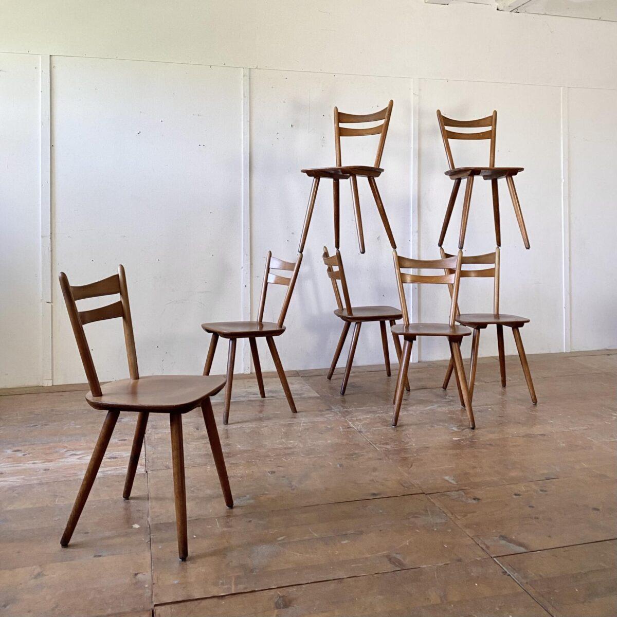 Deuxieme.shop 60er Jahre Stühle. 16 Stabellen Stühle aus Buchenholz. Mit gedrechselten konischen Rundholz Stäben. Preis pro Stuhl. Die Stühle sind in stabilem Zustand. Diverse kleinere Schrammen und Gebrauchsspuren. Ein Hersteller ist nicht ersichtlich.