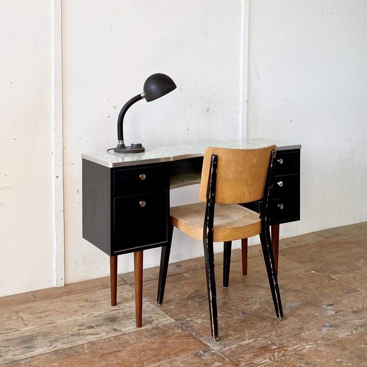 Deuxieme.shop Art déco. Kleiner Schreibtisch oder Schminktisch mit Aluminium Kanten. Der Tisch könnte von der Zürcher Firma Schalk, aus den 50er Jahren, sein. Tischblatt und Ablage aus grün gemustertem Kelko, Schubladenkorpus mit schwarzem Kunstharz belegt. Die Griffe sind etwas abgegriffen und teilweise verbogen. Die Aluminiumkante ist an einer Ecke gebrochen, hält aber fest am Tischblatt. Die konischen Rundbeine sind aus Buchenholz, gebeizt und lackiert.