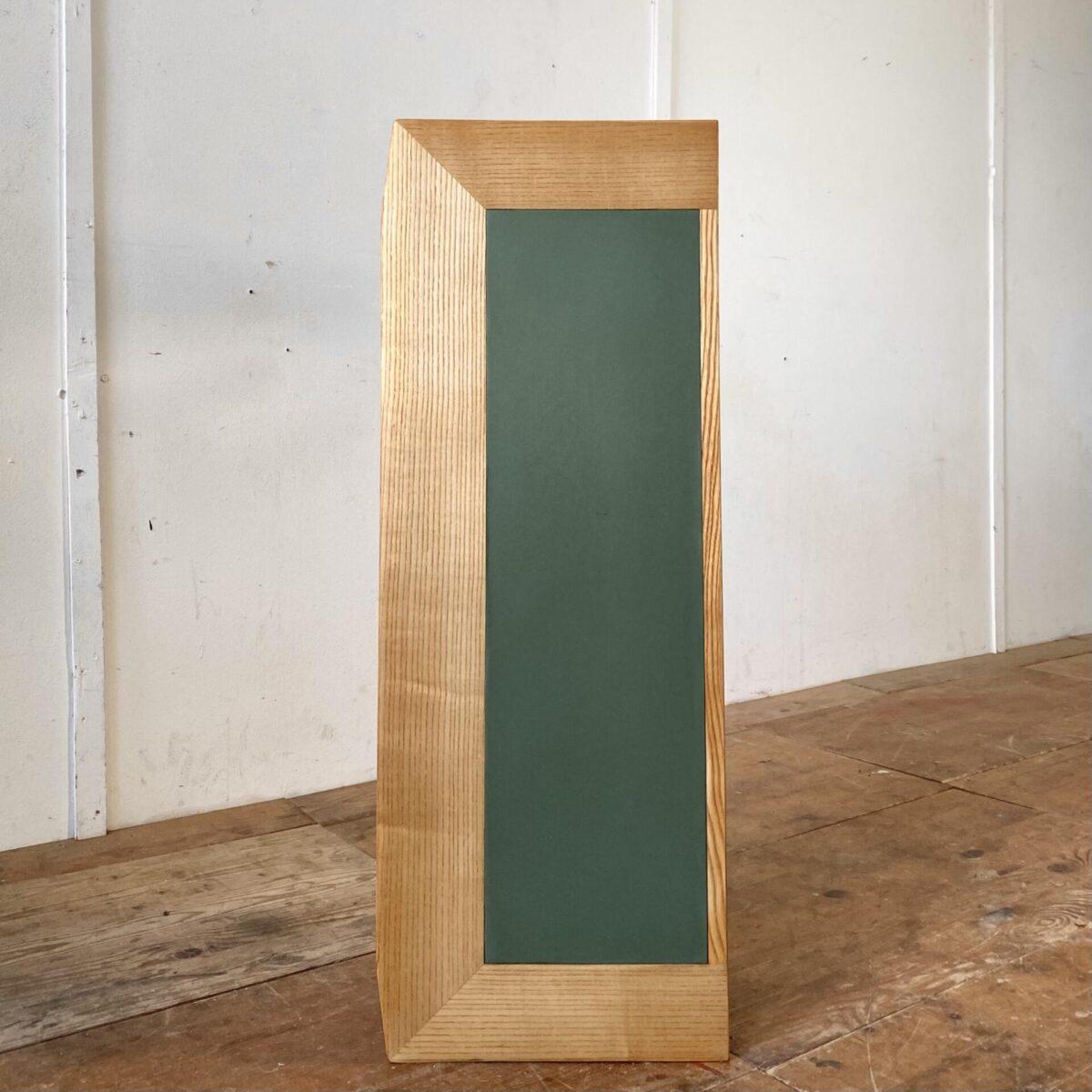 Deuxieme.shop Kleine Kommode mit 6 Schubladen aus Eschenholz. 100x37cm Höhe 68.6cm. Die Konischen Schrägbeine lassen das Möbel leicht wirken. Ins Deckblatt ist eine grüne Einlage eingearbeitet, Kelko oder ein etwas weicherer Kunststoff. Seitlich betrachtet ist der Möbelkorpus Trapezförmig. Die Schubladengriffe sind etwas dunkler, ich tippe auf Ulmenholz. Auch die Rückseite der Kommode ist als Sichtseite verarbeitet.