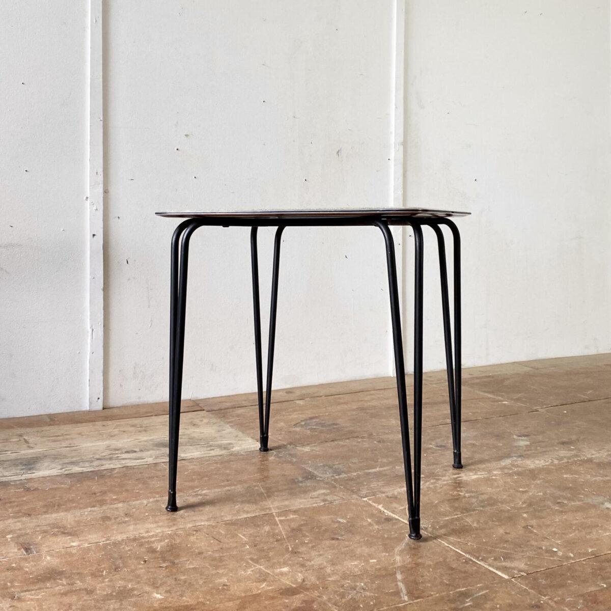 Deuxieme.shop 60er Jahre Tisch. Kleiner kompakter Küchentisch mit schwarzen konischen Stahlbeinen. 66x66cm Höhe 67cm. Das Werzalit Tischblatt ist grün-schwarz meliert, zur Kante hin verjüngt, und mit einer Aluminiumkante eingefasst. Der Tisch eignet sich auch als Gartentisch oder Balkontisch. Die Hairpin artigen Tischbeine sind schwarz lackiert und mit Gummifüssen bestückt. Die Tischkante, aus Alu, ziert ausserdem ein feines eingepresstes Kunststoff Filet.