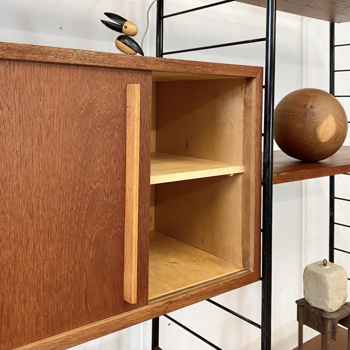 Deuxieme.shop Stringregal Niessen. Midcentury Teak Regal mit Schiebetüren Korpus. 160x36cm Höhe 171cm. Das Bücherregal ist aus den 60er Jahren, ähnlich den Stringregalen, ein Hersteller ist nicht ersichtlich. Schöner allgemein Zustand mit kleineren Alters Abnutzungen. Der Korpus Innenraum, mit Tablar, ist Ahorn furniert. Die Metall Leitern sind schwarz lackiert, an diversen Stellen ist die Farbe etwas abgewetzt, hauptsächlich im Bereich der Tablar Haken.